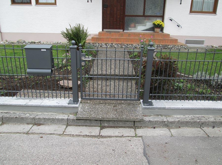 Grauer Zaun mit Eingangstür